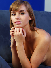 Natalia G sprawls on the sofa and showcases her smooth long legs and pink shaven pussy.